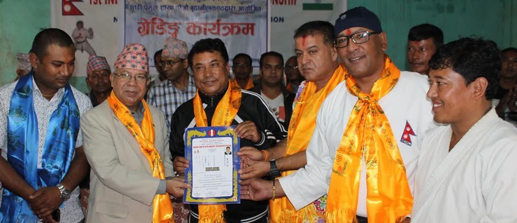 पूर्व प्रधानमन्त्री माधवकुमार नेपालडोजो अध्यक्ष बालकृष्णश्रेष्ठ (दाया) लाई मानार्थ तेश्रो डानको प्रमाणपत्र प्रदान गर्दै ।